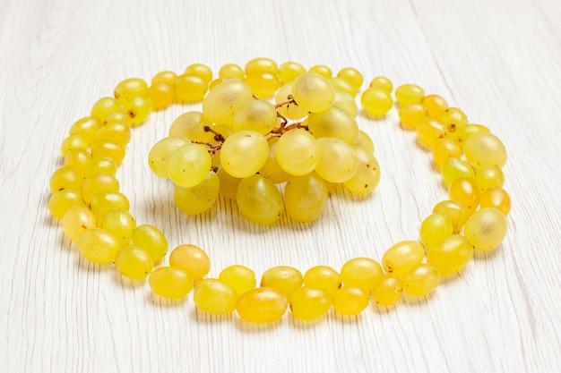 Вид спереди свежий зеленый виноград, образующий круг на белом столе, цвет фруктового вина, спелого сока