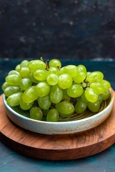 正面図新鮮な緑のブドウは紺色の机の上のプレートの内側のジューシーな果物をまろやかにします。
