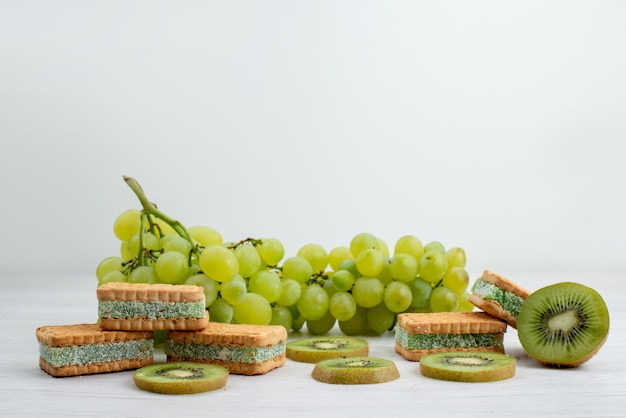 A front view fresh green grapes sour juicy and mellow with cookies and kiwis on the white background fruit ripe plant green
