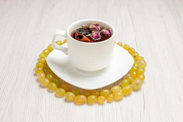 Uva verde fresca di vista frontale con la tazza di tè sull'uva passa di colore del succo di frutta dolce della scrivania bianca