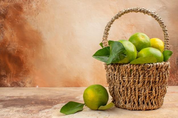 Vista frontale mandarini verdi freschi all'interno del cesto su sfondo chiaro frutta dolce succo fotografico colore natale