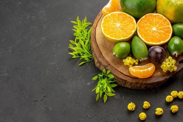 Mandarini verdi freschi di vista frontale con feijoas e caramelle sullo spazio scuro