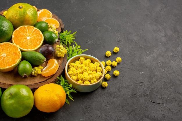 Mandarini verdi freschi di vista frontale con feijoas sullo spazio scuro