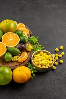 暗い机の上のフェイジョアと新鮮な緑のみかん 柑橘系のエキゾチックなフルーツ グリーン