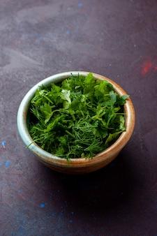 Вид спереди свежая зелень внутри круглой миски на темном столе, зеленые свежие овощные продукты