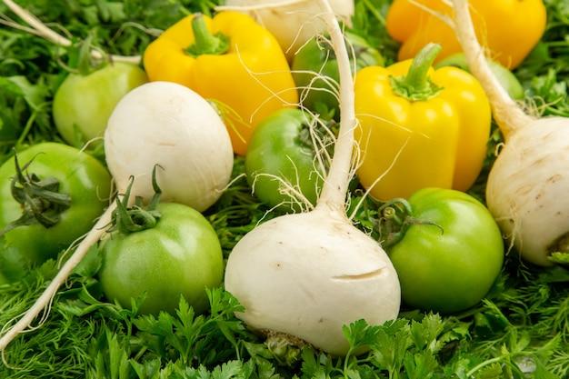 Vista frontale verdure fresche con pomodori verdi ravanelli e peperoni su sfondo bianco pasto dieta sana vita colore insalata foto