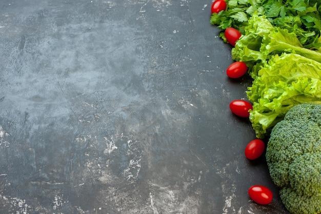 Свежая зелень с маленькими помидорами на сером столе, вид спереди, спелый салат