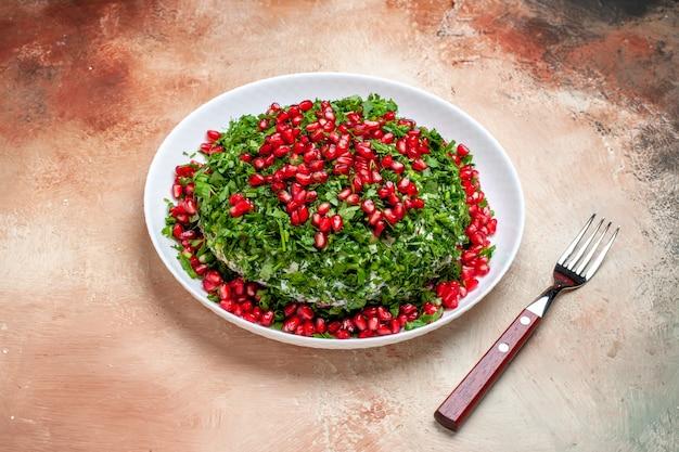 Verdure fresche di vista frontale con melograni sbucciati sulla farina verde di colore della frutta della tavola leggera