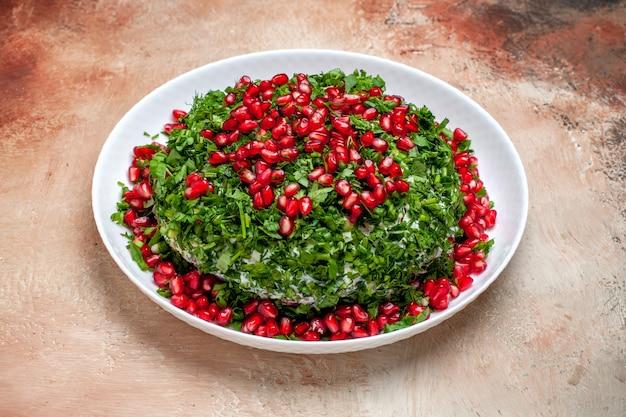 Vista frontale verdure fresche con melograni sbucciati sul tavolo luminoso di colore verde della frutta
