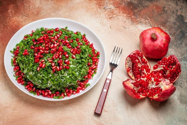 Front view fresh greens with peeled pomegranates on a light table green fruit meal