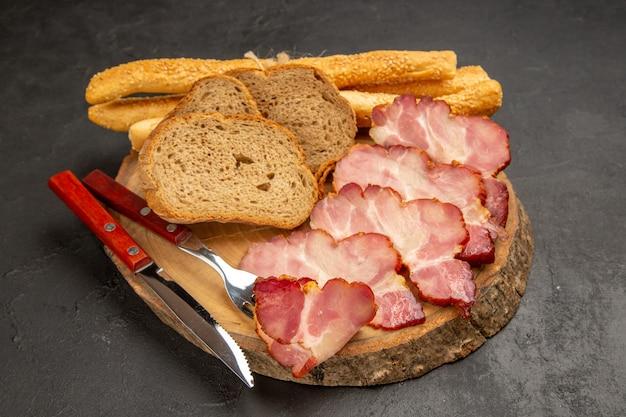 Vista frontale fette di prosciutto fresco con fette di pane e panini su spuntino scuro carne foto a colori pasto alimentare