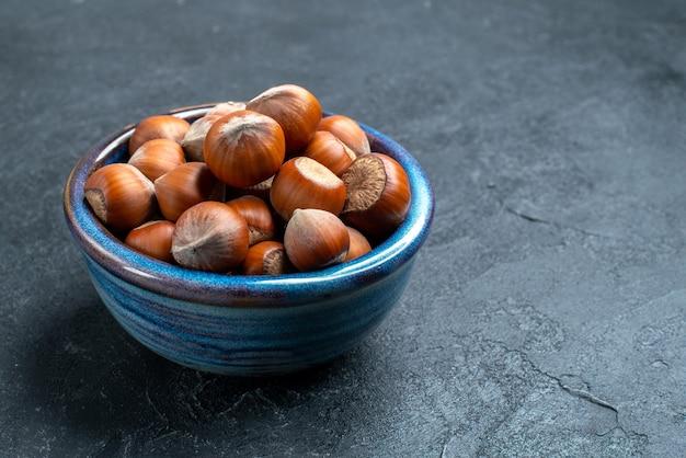 暗い表面の小さな鍋の中の新鮮なヘーゼルナッツの正面図