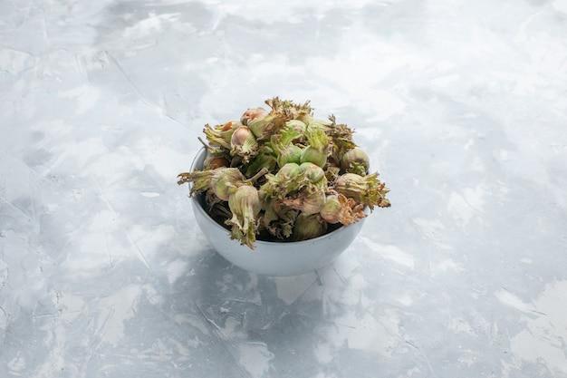 白い机の上の小さな鍋の中の新鮮なヘーゼルナッツの正面図ナッツヘーゼルナッツスナックの木の植物