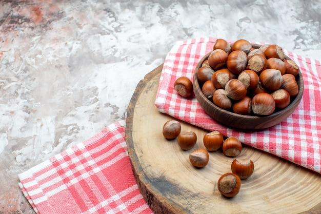 전면 보기 흰색 배경에 분홍색 수건이 있는 신선한 헤이즐넛 너트 식물 스낵 사진 부엌 나무 호두