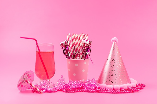 A front view fresh juice with straw along with birthday cap and stick candies on pink