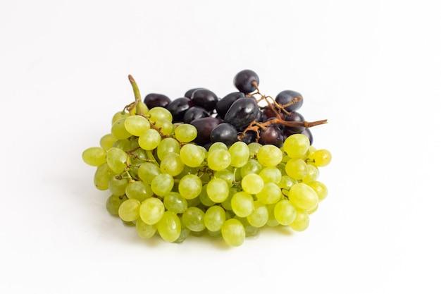 正面の白い机の上の新鮮なジューシーなブドウのまろやかな果物