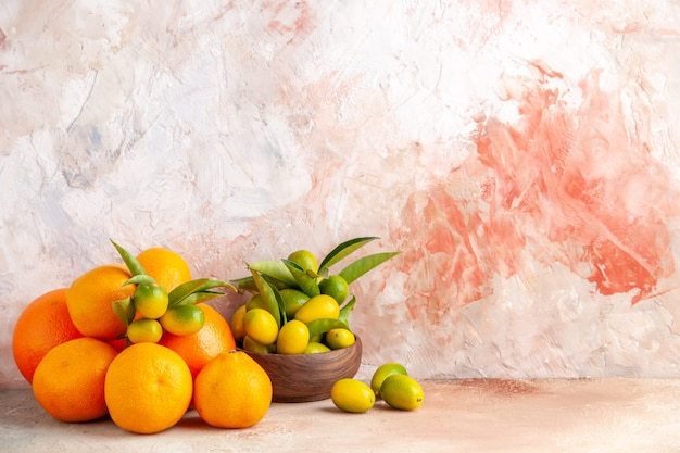 Front view of fresh kumquats in a brown pot and tangerines on colorful bakground