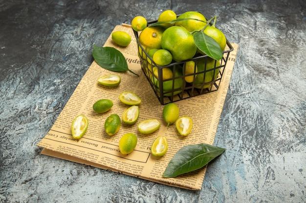 Vista frontale di kumquat e limoni freschi in un cestino nero su giornali su sfondo grigio immagine stock