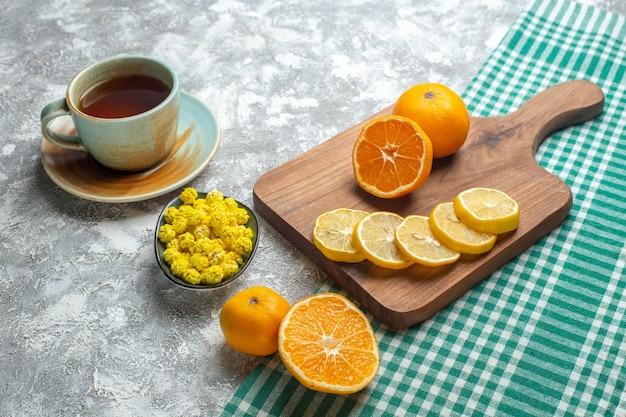 正面図明るい表面にキャンディーとお茶のカップと新鮮なレモンスライス