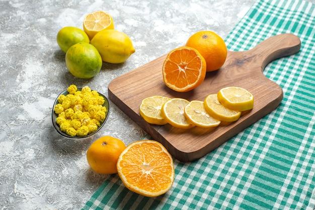 Вид спереди свежие дольки лимона с конфетами на светлой поверхности