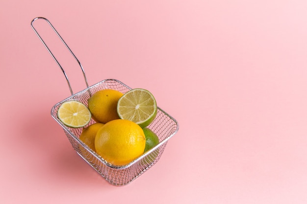 Front view of fresh lemons citruses inside fryer on pink wall