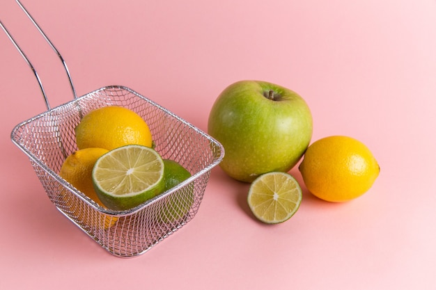 Front view of fresh lemons citruses inside fryer with apple on the pink wall