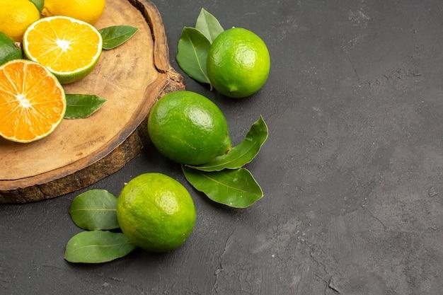暗い机の上の新鮮なレモンの正面図フルーツライムサワーシトラス