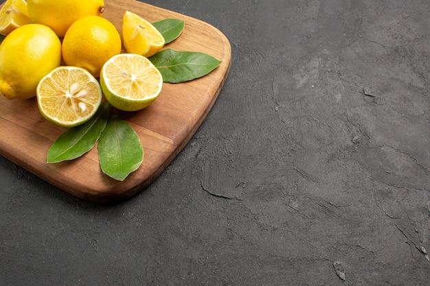 Vista frontale limoni freschi frutta acida sullo sfondo scuro