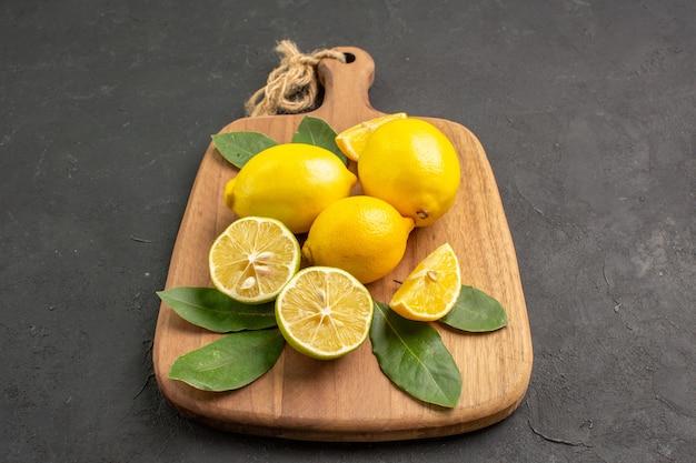 Vista frontale limoni freschi frutta acida su sfondo grigio scuro
