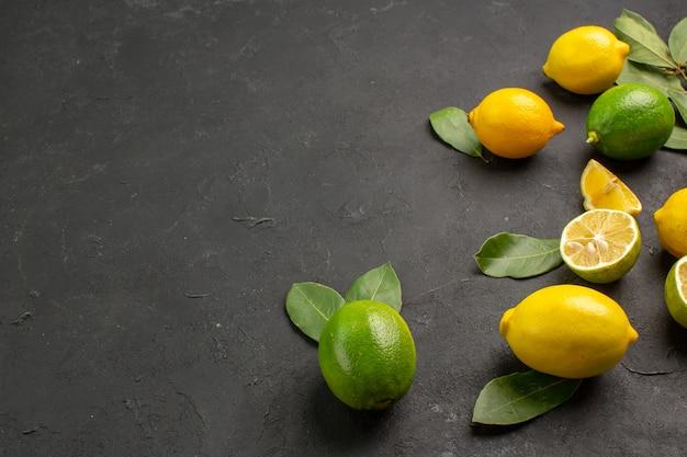 暗い机の上の正面図新鮮なレモン酸っぱい果物