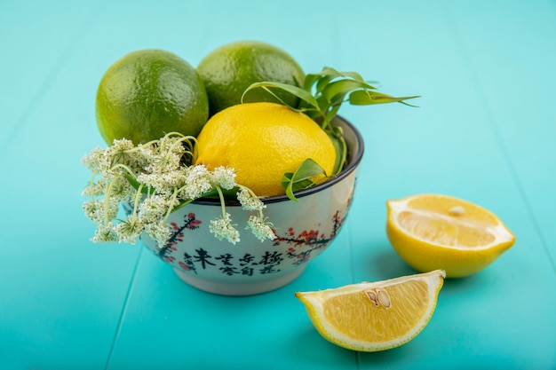 Front view of fresh lemons with tarragon on a bowl with slices of lemon on blue surface