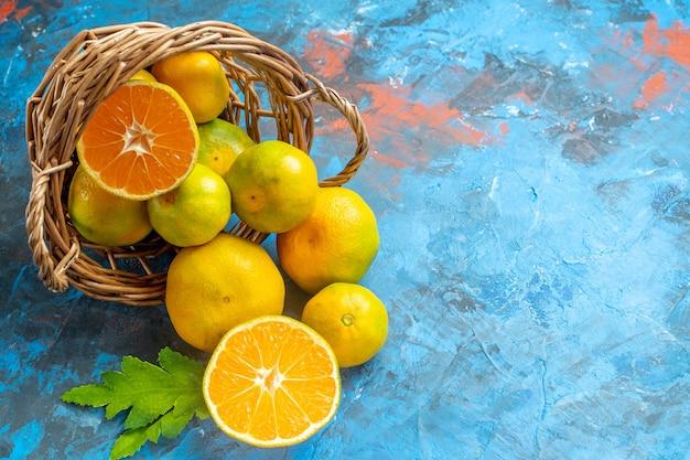 Mandarini freschi di vista frontale sul canestro di vimini sulla superficie blu con lo spazio della copia