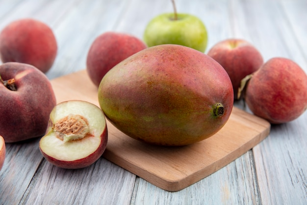 Front view of fresh mango on a wooden kitchen board with fresh fruits such as apple peach on grey wooden surface
