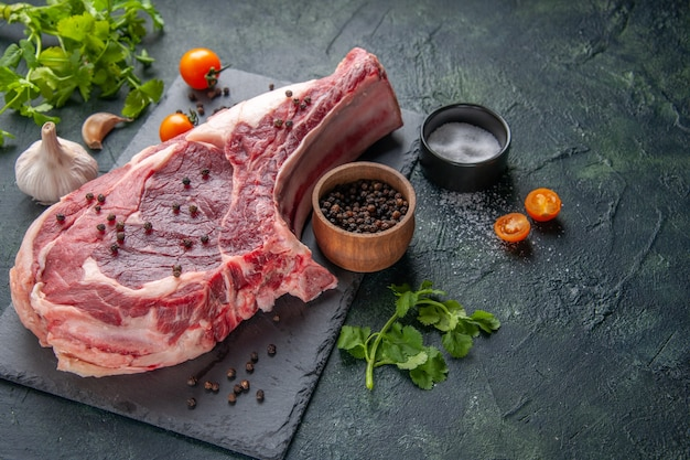 Вид спереди ломтик свежего мяса сырое мясо с перцем и зеленью на темной куриной муке цветная еда животное мясник фото барбекю