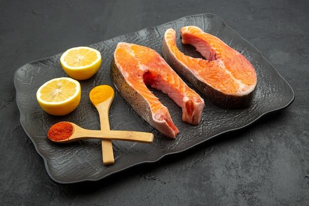 Vista frontale fette di carne fresca all'interno del piatto con fette di limone su sfondo scuro piatto cibo farina di pesce foto costola animale