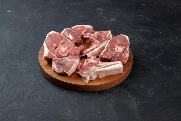 어두운 배경 음식 신선도 동물 소 식사 음식 부엌에 둥근 나무 책상에 신선한 고기 조각 생고기를 전면 보기