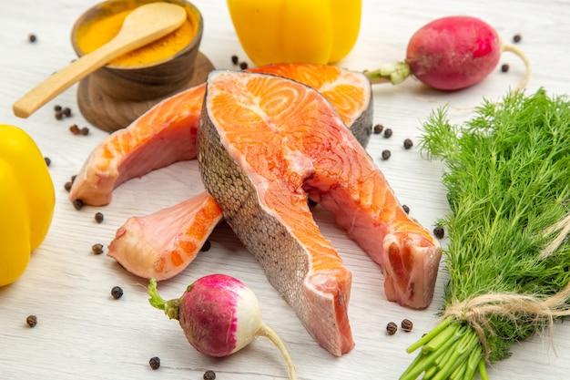 Vista frontale fette di carne fresca con verdure e peperoni su uno sfondo bianco costolette di pesce foto piatto cibo pasto animale