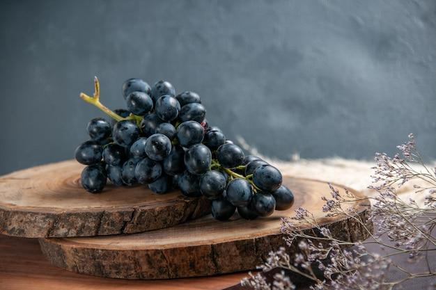 Vista frontale uva fresca e dolce frutti scuri sulla superficie scura uva da vino frutta matura pianta fresca