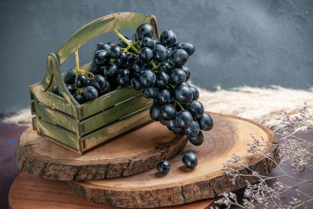 Вид спереди свежий спелый виноград темные фрукты на темной поверхности вино виноградные плоды спелые свежие древесные растения