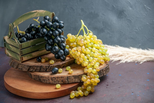 Vista frontale uva fresca e dolce frutti scuri e verdi sulla superficie scura frutta dell'uva da vino pianta fresca matura dell'albero