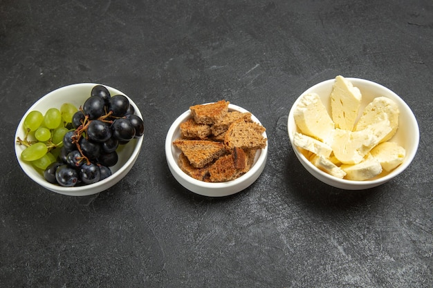 Вид спереди свежий спелый виноград с белым сыром и нарезанным темным хлебом на темном фоне блюдо для еды с молочными фруктами