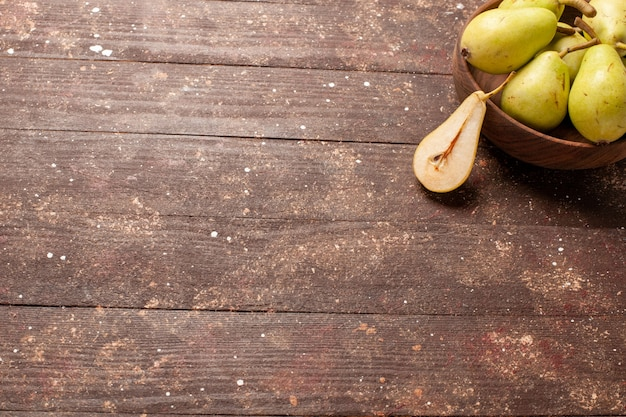 茶色の机の上に緑とジューシーな新鮮なまろやかな梨の正面図