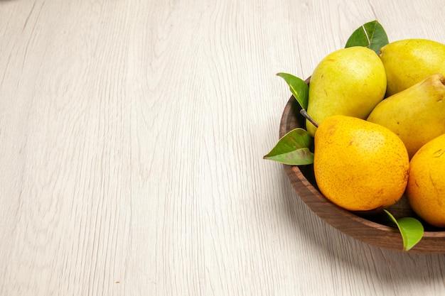 Vista frontale pere fresche e dolci frutti dolci all'interno del piatto sulla scrivania bianca frutti gialli freschi dolci maturi