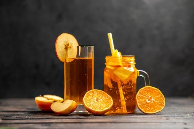 Vista frontale di un delizioso succo naturale fresco in due bicchieri che mette a mano lime di frutta con un tubo su sfondo nero