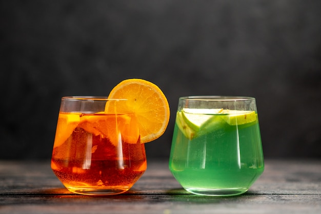 Front view of fresh natural delicious juice in two glasses with fruit limes on black background