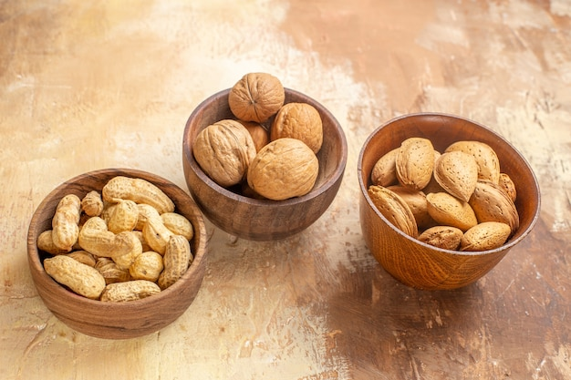 木製デスクナットヘーゼルナッツピーナッツのプレート内の新鮮なナッツの正面図