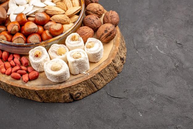 Vista frontale di arachidi noci fresche e altri dadi sulla superficie scura
