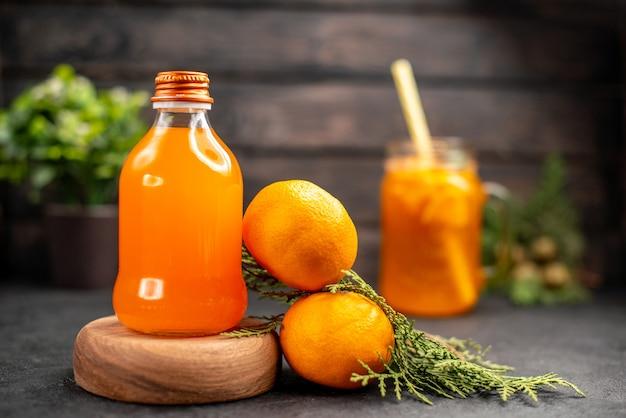 Succo d'arancia fresco di vista frontale in bottiglia sul bordo di legno