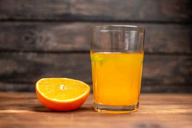 Vista frontale del succo d'arancia fresco in un bicchiere servito con menta e lime all'arancia su un tavolo di legno