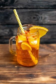 Front view fresh orange juice inside can on brown wooden desk drink photo cocktail color fruit bar